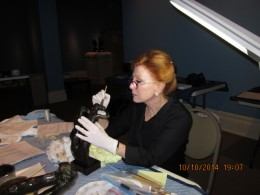 Associate Conservator Terri Hofstadter uses a soft brush to get to the dust in 'The Night (Double Figure).'