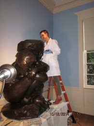 Conservator Mina Thompson applying wax to Rodin's 'Caryatid with Stone.' The waxes protect the patinas on the surface of the bronzes; they are colored to match the patinas.